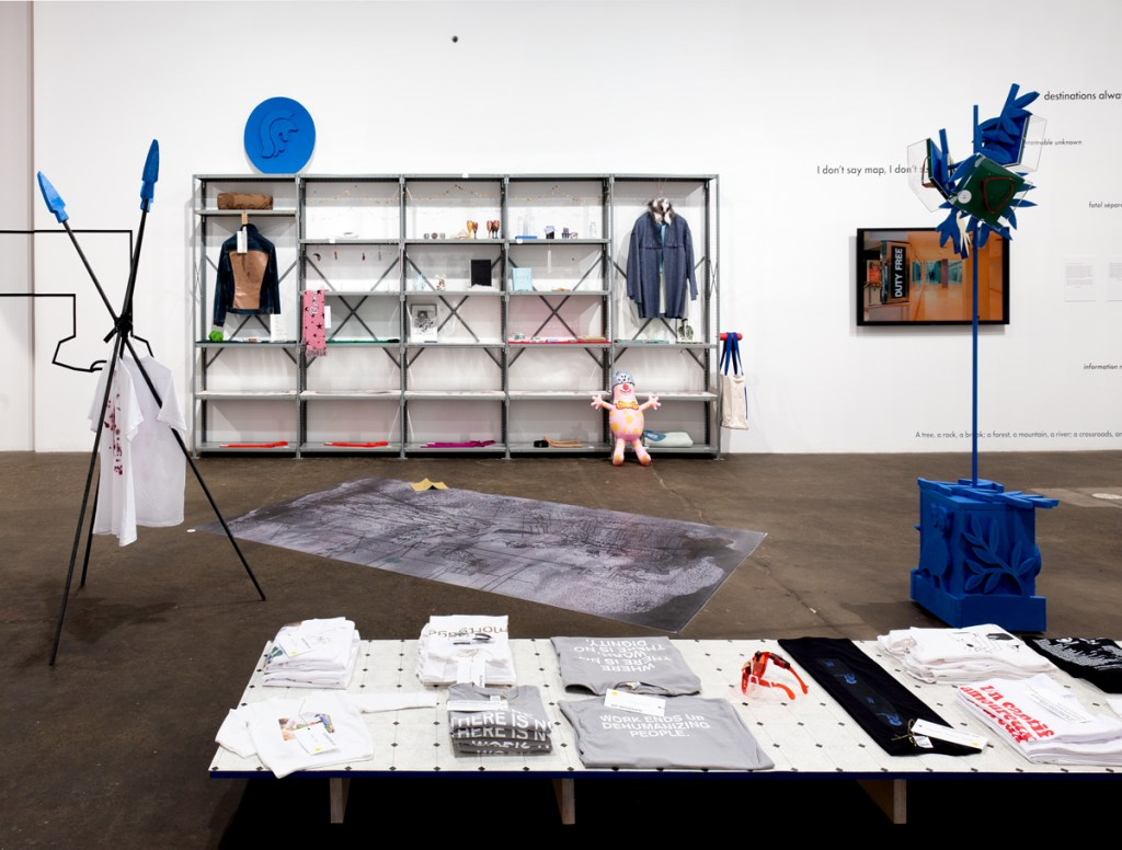 'THE GEO POLITICS OF MONETIZED AIRSPACE — Come Fly with Me, I meet You by the Airside Gucci Concession at 4, Fox Fur Hat', Sarah Staton Super Store (2016) installation view, Midway Contemporary Art, Minneapolis. C21ST RECENT HISTORY displayed on shelving unit